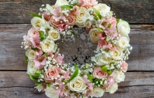 Roses wreath on wooden background.