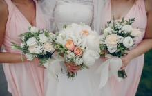 bride and bridesmaid standing with flowers